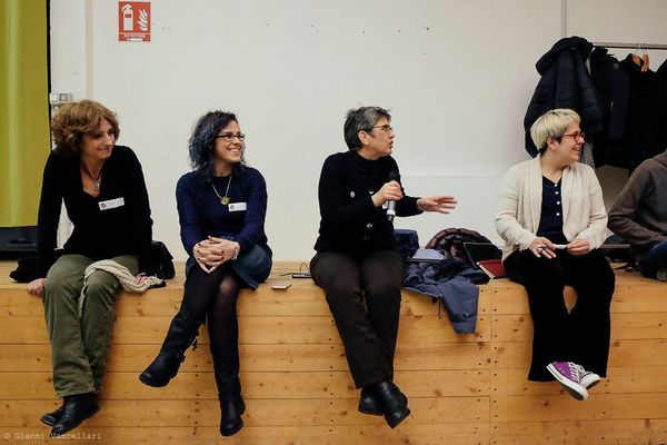 Four women seated on a low wall at a WordPress meetup.